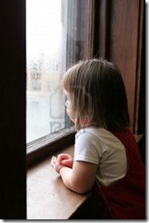 3194827-little-girl-looking-out-the-window-at-a-rainy-day-outside